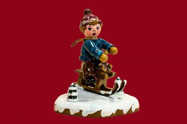 Winterkind Schlittenfahrer
